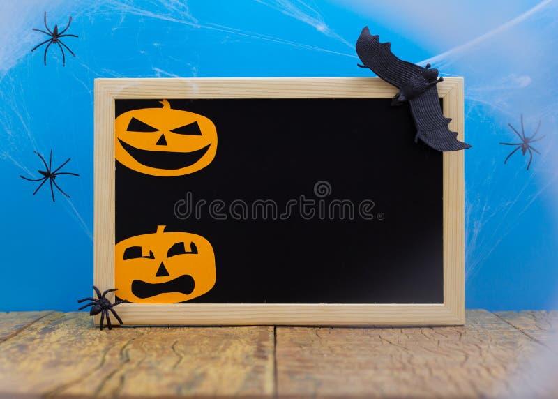 Halloween-achtergrondconcept Het lege bord met decordocument sneed de gezichten van de hefboomo pompoen, spinneweb op houten lijs royalty-vrije stock fotografie