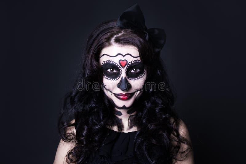 Halloween affronta l'arte - la donna con il cranio compone sopra il nero fotografia stock