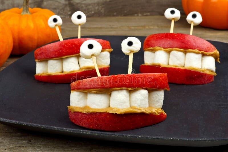 Halloween apple, marshmallow, peanut butter monster teeth snack stock photos