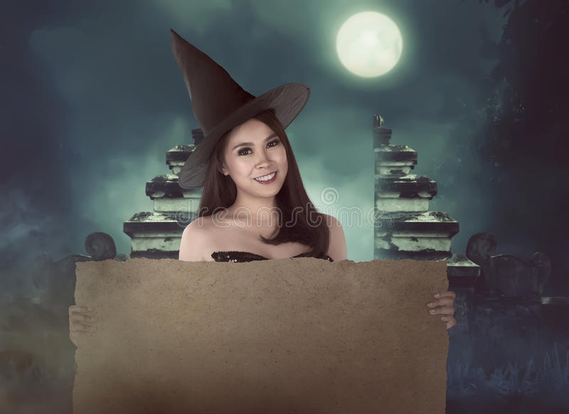 Halloween asian witch with hat holding blank paper stock image