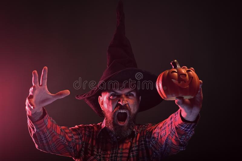 Halloween autumn holiday celebration. Trick or treat. Hipster in wizard hat holding pumpkin on dark background. Mystery and magic concept. Man with scary face royalty free stock photos