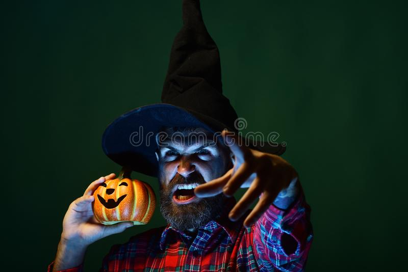 Halloween autumn holiday celebration. Hipster with scary face and jack o lantern. Trick or treat. Mystery and magic concept. Man in wizard hat holding pumpkin stock photo