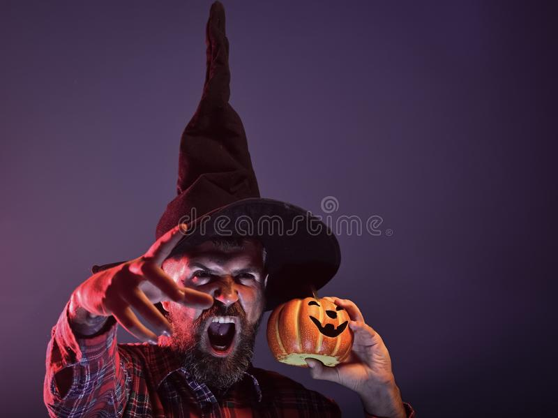 Halloween autumn holiday celebration. Man in witch hat holding pumpkin in red light. Trick or treat. Wizard hipster with scary face and jack o lantern. Mystery royalty free stock photography