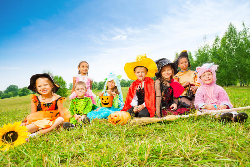 Halloween avec des enfants dans des costumes se reposent dehors photo libre de droits