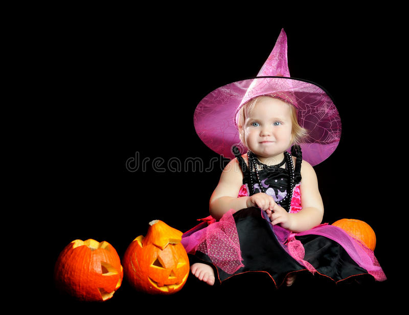 Halloween baby witch with a carved pumpkin. Over black background with smoke stock photos