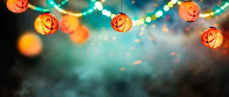 Halloween Background. Beautiful dark forest backdrop with hanging Pumpkin lanterns, smoke, garlands. Halloween magic holiday collage frame Art design. Copy royalty free stock photo