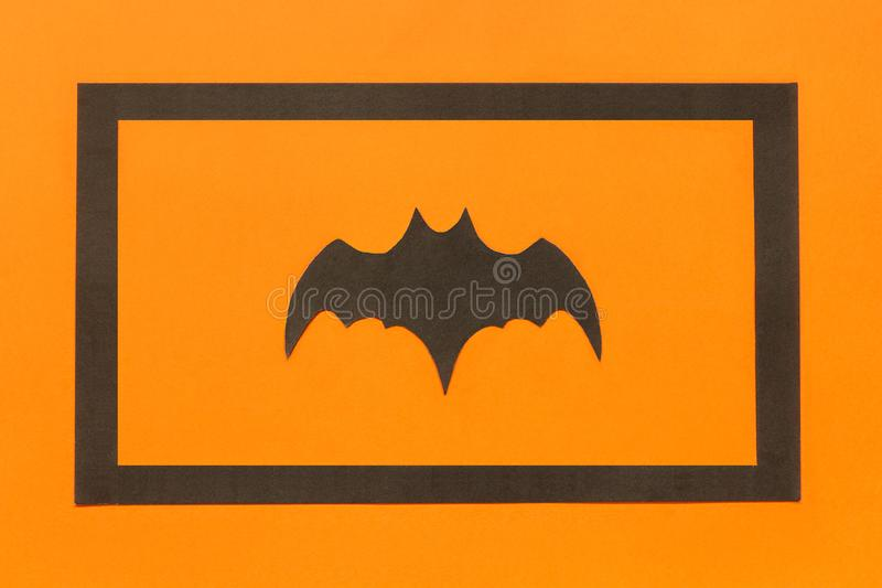 Halloween background. Black paper bat in black frame on orange background royalty free stock photos
