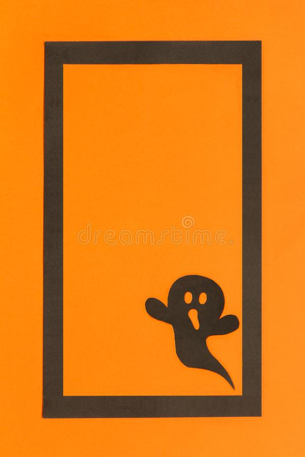 Halloween background. Black paper ghost in black frame on orange background stock photography
