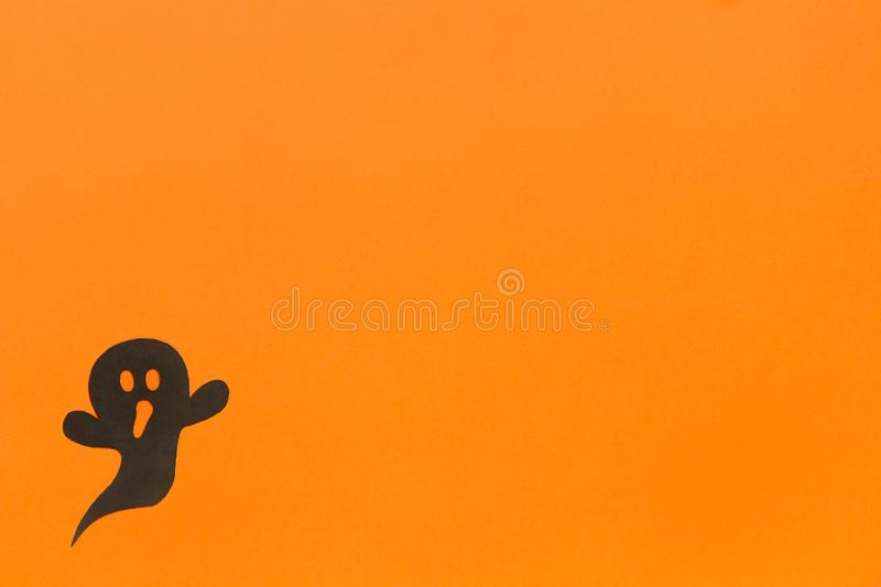Halloween background. Black paper ghost on orange background stock images