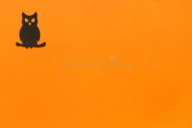Halloween background. Black paper owl in black frame on orange background stock photos
