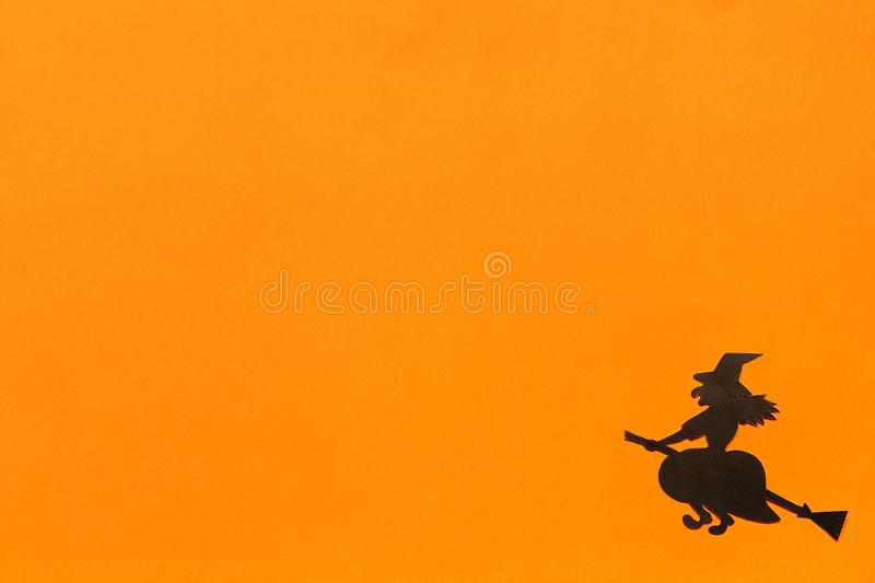 Halloween background. Black paper witch on orange background stock images