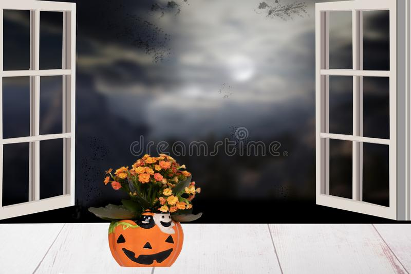 Halloween background. Bright table with flowers in a yellow porcelan pumpkin in front of dark blue scary abstract halloween royalty free stock images