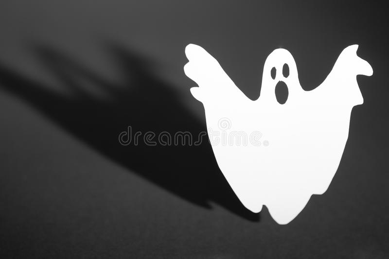 Halloween background concept. Funny ghost doing boo gesture and graphic shade behind on dark table royalty free stock image