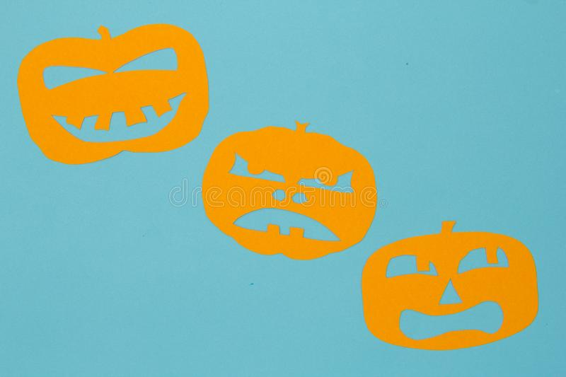 Halloween background concept. Minimalism flat lay view of Cut out paper of jack O pumpkin funny faces on blue table. Halloween background decoration holiday stock photography