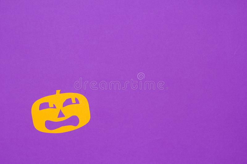 Halloween background concept. Minimalism flat lay view of Cut out paper of jack O pumpkin scared face on purple table. Halloween background decoration holiday royalty free stock photo