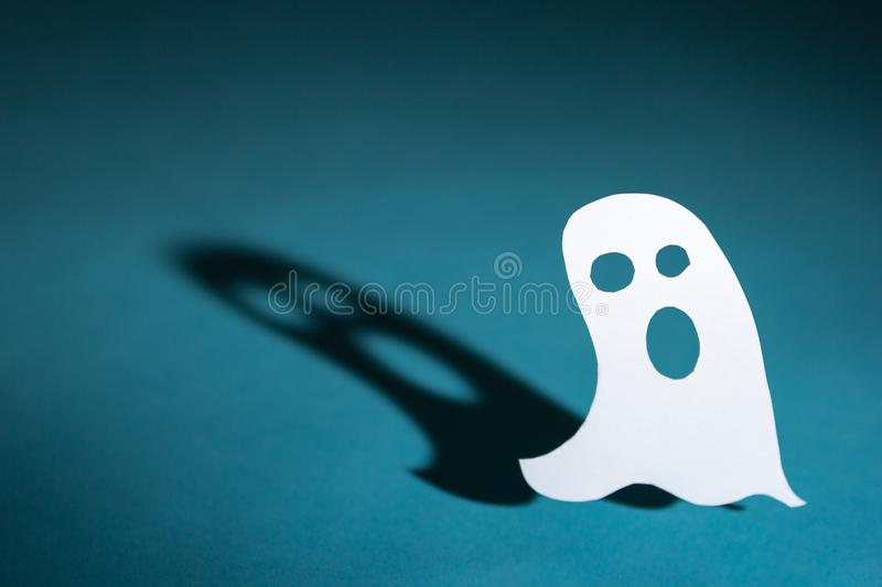 Halloween background concept. Cut out paper ghost and graphic sh. Halloween background decor holiday concept. Cut out paper ghost and graphic shadow, funny face royalty free stock photo