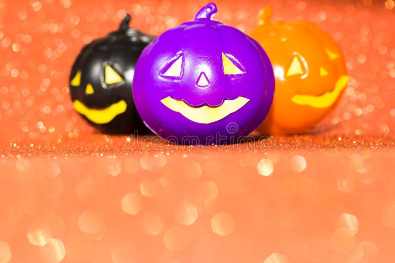 Halloween background concept. Jack O pumpkin faces on bright glitter orange backdrop. stock photo