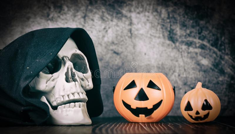 Halloween background decorated holidays festive concept - jack o lantern pumpkin halloween decorations with skull on dark royalty free stock images