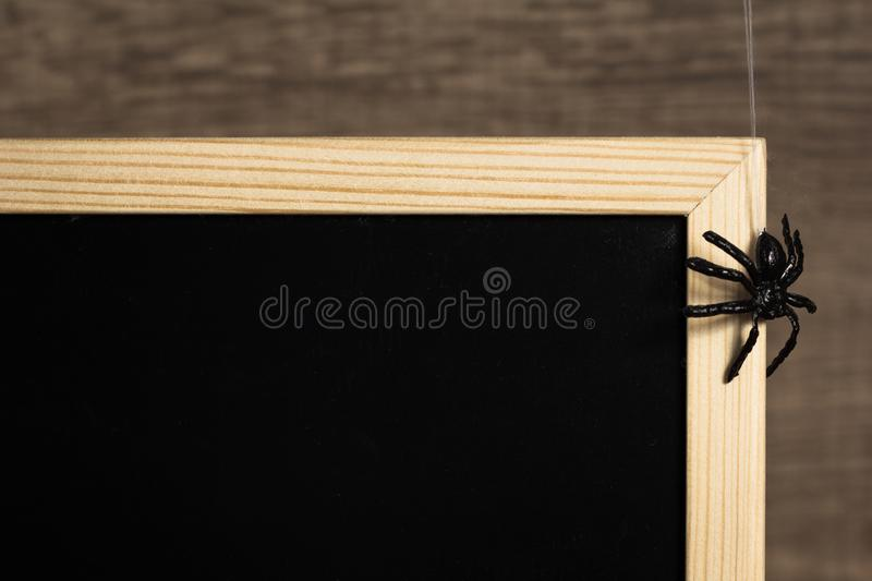 Halloween background concept. Detail of blackboard and black spider hanging on spider web stock photo
