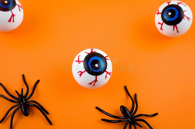 Halloween background with eyes and spiders. Halloween with many candy eyes and spiders on orange background, autumn holidays concept, harvesting, copy space, top royalty free stock photography