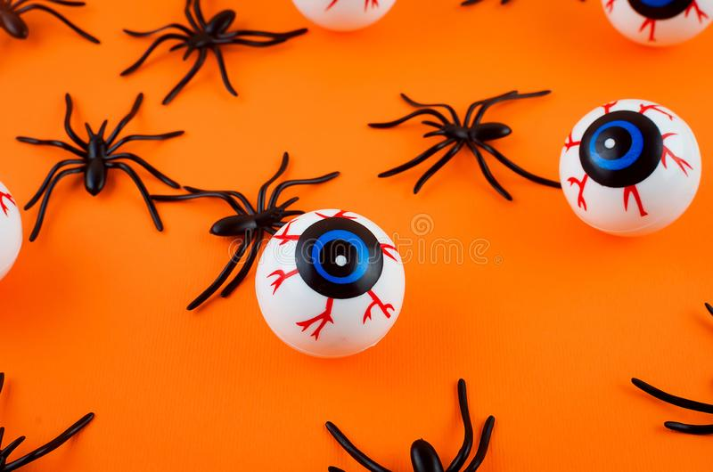 Halloween background with eyes and spiders. Halloween with many candy eyes and spiders on orange background, autumn holidays concept, harvesting, copy space, top royalty free stock images