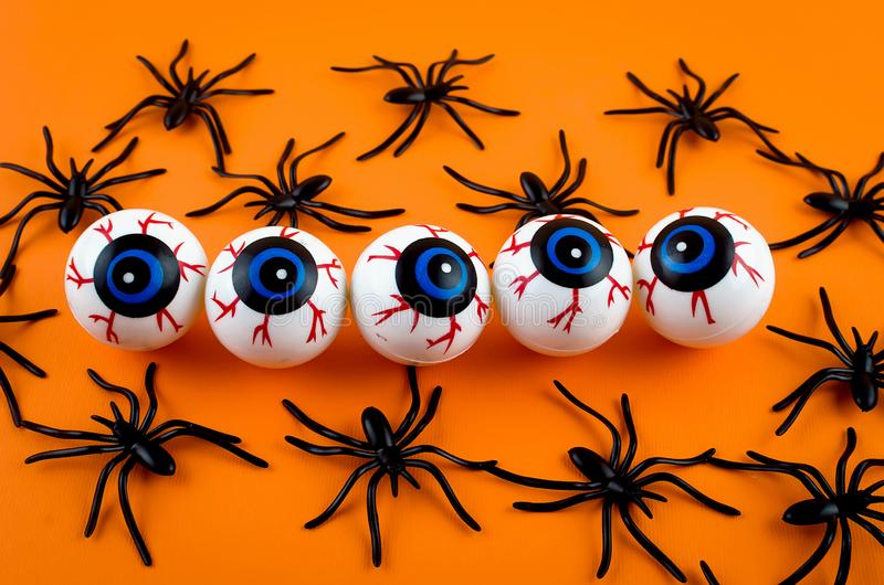 Halloween background with eyes and spiders. Halloween with many candy eyes and spiders on orange background, autumn holidays concept, harvesting, copy space, top stock photos