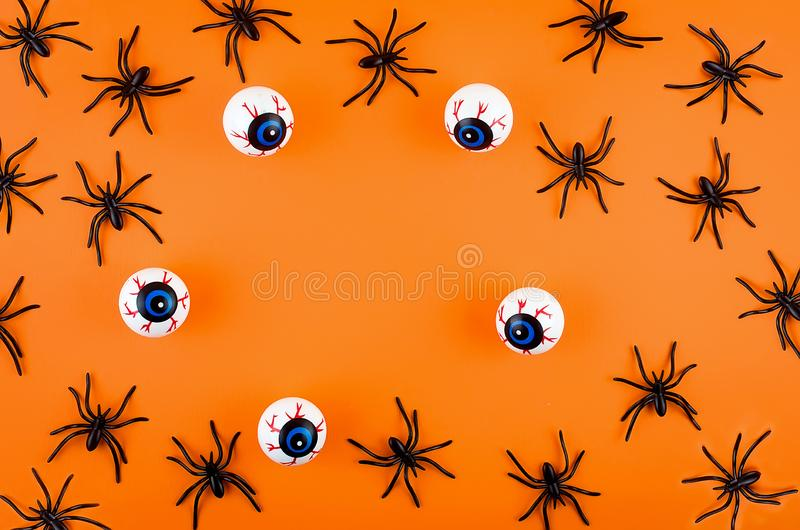 Halloween background with eyes and spiders. Halloween with many candy eyes and spiders on orange background, autumn holidays concept, harvesting, copy space, top stock photo