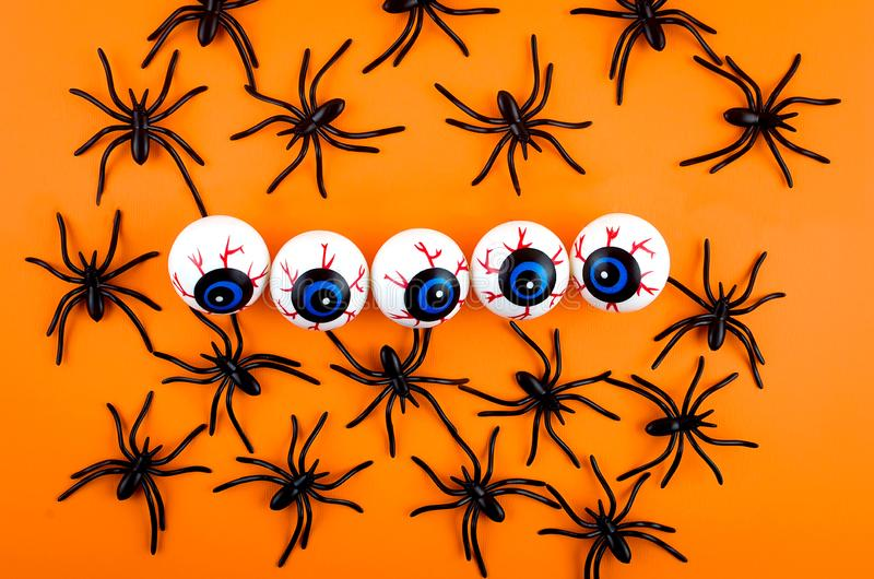 Halloween background with eyes and spiders. Halloween with many candy eyes and spiders on orange background, autumn holidays concept, harvesting, copy space, top stock photography