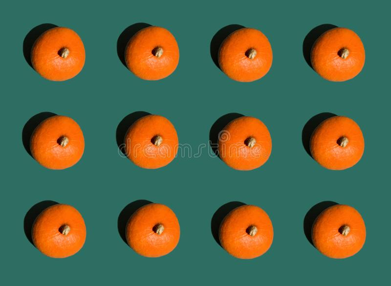 Halloween background geometrical rows of bright orange pumpkins on dark green. Seamless pattern. Pop art style. Creative concept royalty free stock image