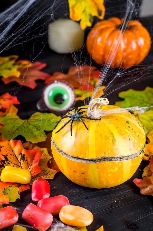 Halloween background with gingerbread, pumpkins and candles. Halloween decorations,pumpkins, variety of gingerbreads,, spider and cobweb on black background stock photography