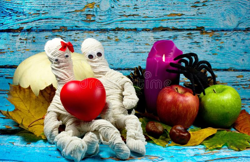 Halloween background. Mummies in love, lilac candle, white pumpkin, green and red apple , black spider and autumn leaves on blue background stock photos