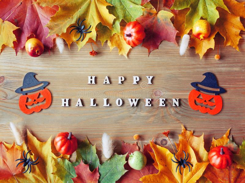 Halloween background. Happy Halloween letters with seasonal leaves and smiling jack decorations as symbols of Halloween royalty free stock photo