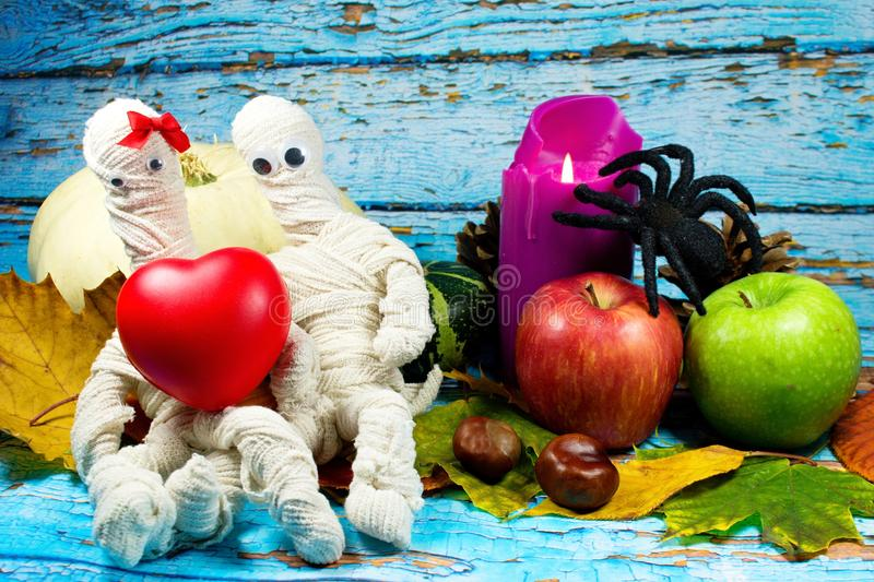 Halloween background. Mummies in love, lilac candle, white pumpkin, green and red apple , black spider and autumn leaves on blue background stock image