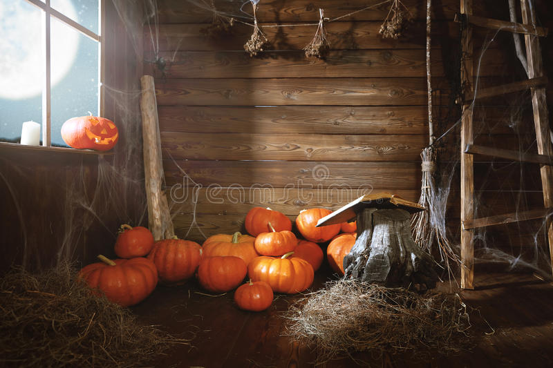 Halloween background. old wooden hut witches barn. With pumpkins, cobwebs, magic book, broom stock images