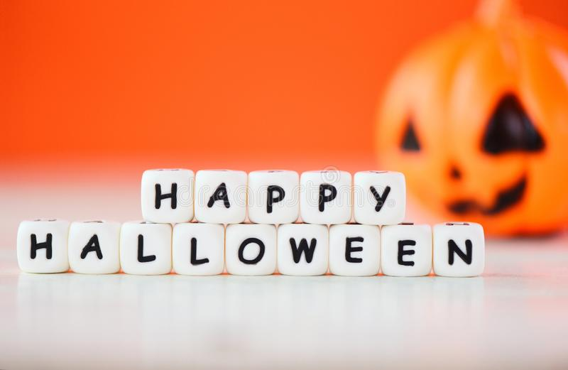 Halloween background orange with word blocks happy halloween decorations and pumpkin jack o lantern funny spooky on white wooden royalty free stock image
