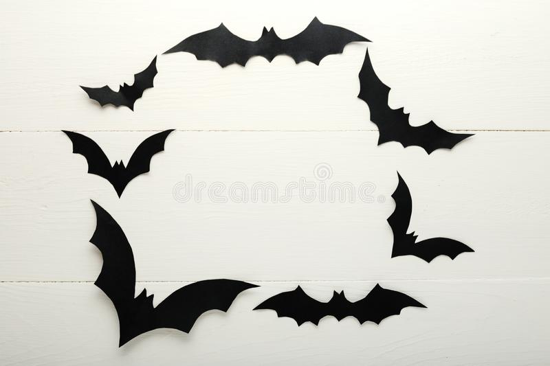 Halloween background with paper bats on white wooden background. Frame. Halloween holiday decorations. Flat lay, top view, copy stock photos