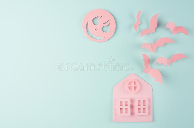 Halloween background - pink house and flock fly bats, spooky face moon as cut cartoon on pastel mint paper background. stock images