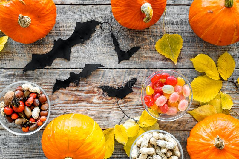 Halloween background. Pumpkins, paper bats and autumn leaves on wooden background top view stock image