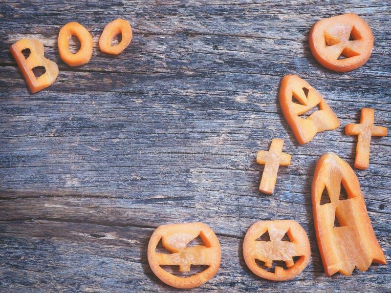 Halloween background.Scarved jack-o-lantern and spooky carrots. Halloween background.Carved jack-o-lantern and spooky carrots stock photos