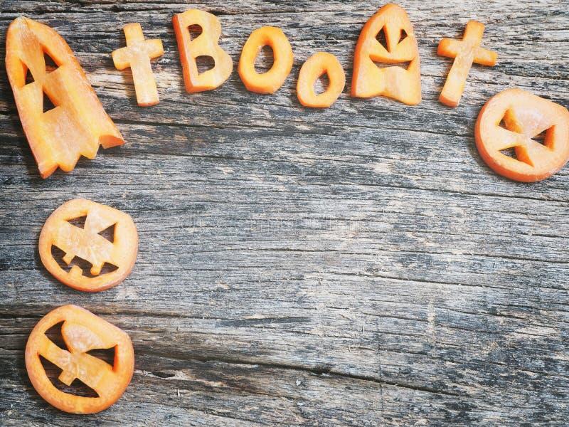 Halloween background.Scarved jack-o-lantern and spooky carrots. Halloween background.Carved jack-o-lantern and spooky carrots royalty free stock images