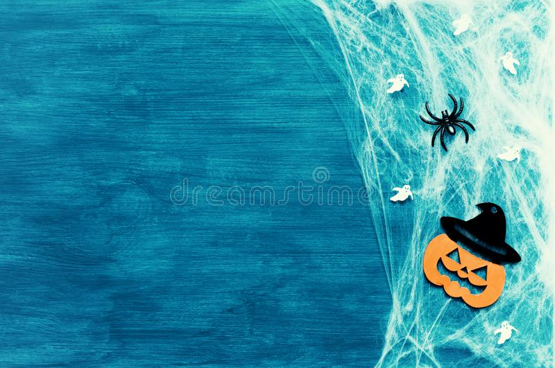 Halloween background. Spider web, spiders and smiling jack decorations as symbols of Halloween on the green background. Halloween background. Spider web, spiders stock image