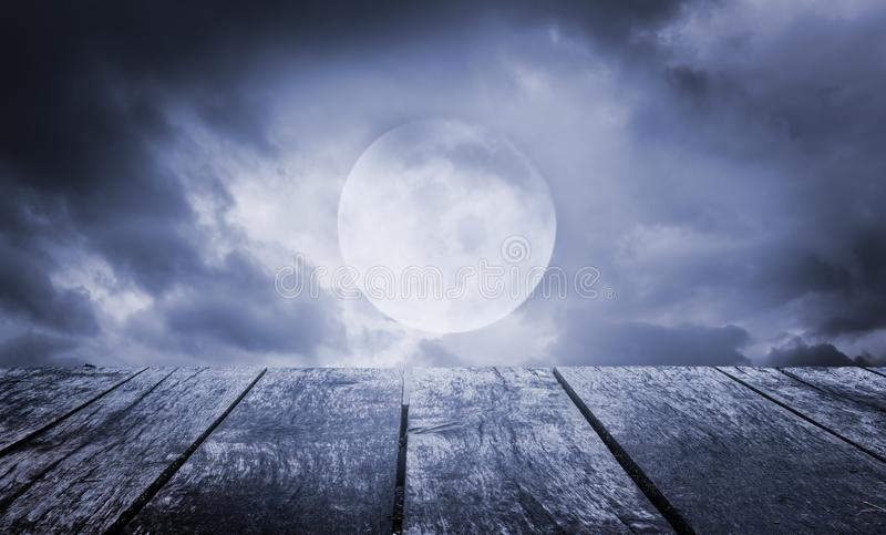 Halloween background. Spooky sky with full moon and wooden table royalty free stock photos