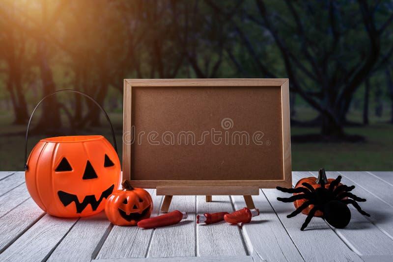 Halloween background. Spooky pumpkin, chalkboard on wooden floor. Halloween background. Spooky pumpkin, Black spider, chalkboard on white wooden floor with moon royalty free stock photo