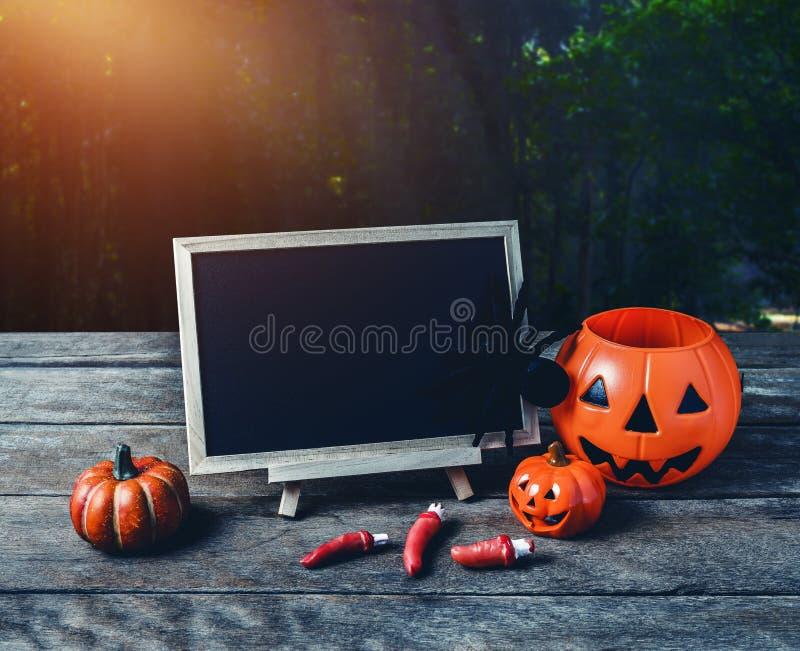 Halloween background. Spooky pumpkin, Black spider, chalkboard o. N wooden floor with moon and dark forest. Halloween design with copyspace stock photos