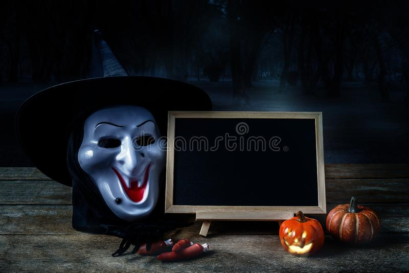 Halloween background. Spooky pumpkin, Black spider, Witch mask,. Chalkboard on wooden floor with moon and dark forest. Halloween design with copyspace royalty free stock images