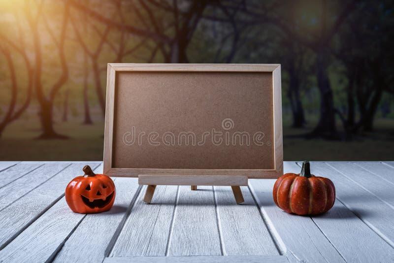 Halloween background. Spooky pumpkin, chalkboard on wooden floor. Halloween background. Spooky pumpkin, Black spider, chalkboard on white wooden floor with moon stock images