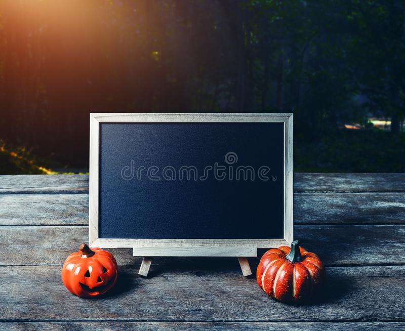 Halloween background. Spooky pumpkin, chalkboard on wooden floor. With moon and dark forest. Halloween design with copyspace royalty free stock images
