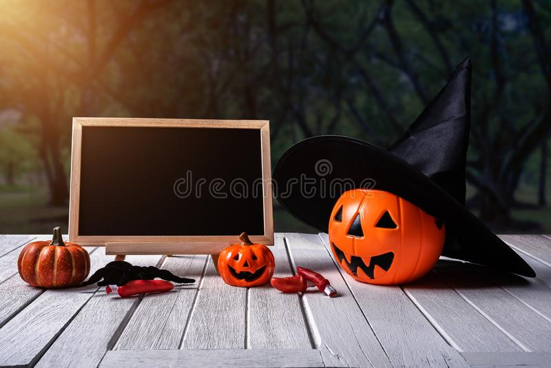 Halloween background. Spooky pumpkin, chalkboard on wooden floor. Halloween background. Spooky pumpkin with Witch hat, Black spider, fingers, chalkboard on white stock photos