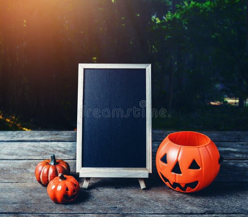 Halloween background. Spooky pumpkin, chalkboard on wooden floor. With moon and dark forest. Halloween design with copyspace stock images