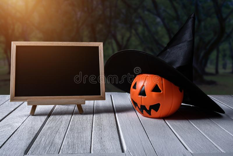 Halloween background. Spooky pumpkin, chalkboard on wooden floor. Halloween background. Spooky pumpkin with Witch hat, chalkboard on white wooden floor with moon royalty free stock photography